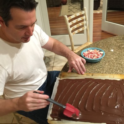 John spreads first layer of dark chocolate